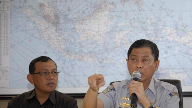 In this photo released by China's Xinhua News Agency, Indonesian Transport Minister Ignasius Jonan, right, speaks at a press conference on AirAsia's missing flight QZ8501 at Juanda International Airport in Surabaya, East Java, Indonesia, Sunday, Dec. 28, 2014. A massive sea search was underway for an AirAsia plane that disappeared Sunday while flying from Indonesia to Singapore through airspace possibly thick with dense storm clouds, strong winds and lightning, officials said. (AP Photo/Xinhua, Syaiful Arif) NO SALES