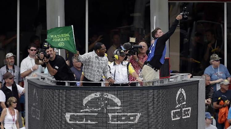 Former Baltimore Ravens linebacker Ray Lewis waves the green to start of the Daytona 500 NASCAR Sprint Cup Series auto race Sunday, Feb. 24, 2013, at Daytona International Speedway in Daytona Beach, Fla.  (AP Photo/Chris O'Meara)