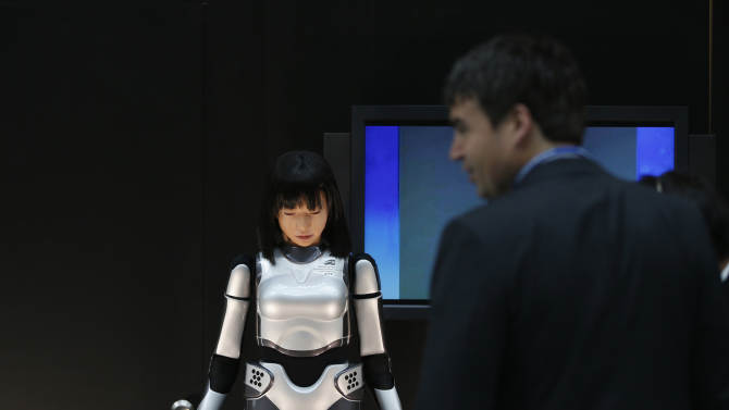Man looks at the HRP-4C Miim humanoid robot at the venue of the Annual Meetings of the International Monetary Fund and the World Bank Group in Tokyo