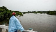 A man on a bridge stares at an overflowed river near Bayamo, 740 kms east of Havana as the residents of eastern Cuba prepare for the arrival of Hurricane Sandy