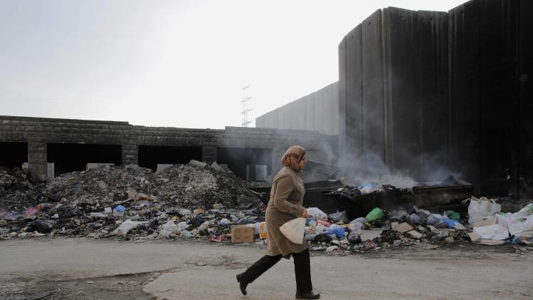 A Palestinian woman walks past garbage discarded near a section of the controversial Israeli barrier, in Shuafat refugee camp in the West Bank near Jerusalem