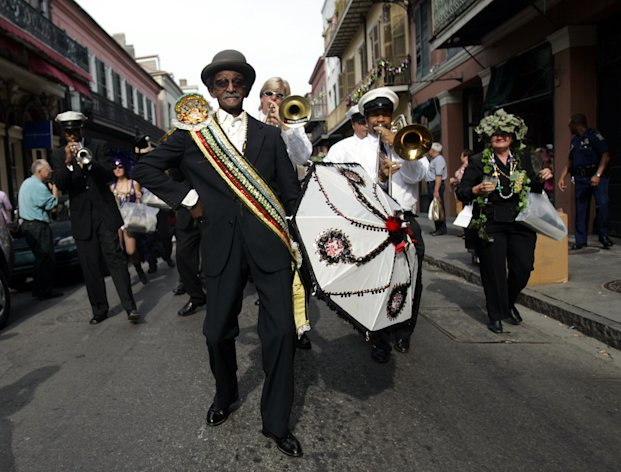 FILE - In this Feb. 17, 2006 file photo, Uncle Lionel Batiste, foreground with umbrella, dances during the Krew of Cork parade through New Orleans' French Quarter. Batiste, the vocalist, bass drummer and assistant band leader of the Treme Brass Band, has died. He was 81. Band leader Benny Jones Sr. says Batiste died Sunday, July 8, 2012. (AP Photo/Carolyn Kaster, File)