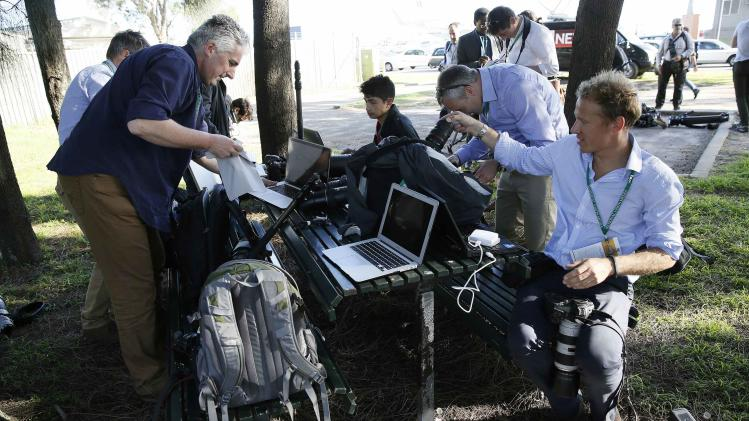 Photographers set up on a picnic table outside Sydney airport after photographing the arrival of Britain's Prince William and family in Sydney