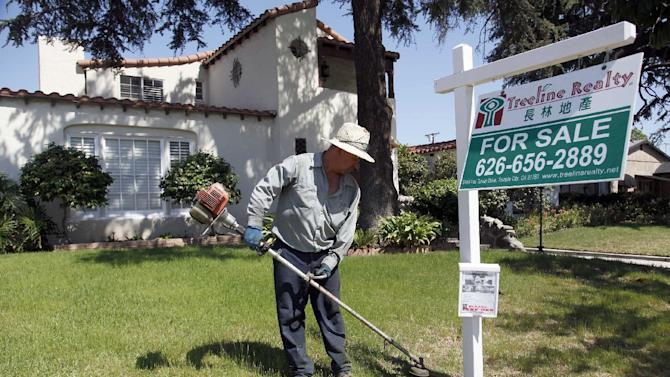 FILE - In this Monday, May 13, 2013 file photo, gardener Jose Lopez trims the front lawn of a home for sale in Alhambra, Calif. U.S. home prices jumped 12.1 percent in April from a year ago, buoyed by strong demand and a limited supply of available homes. (AP Photo/Nick Ut, File)
