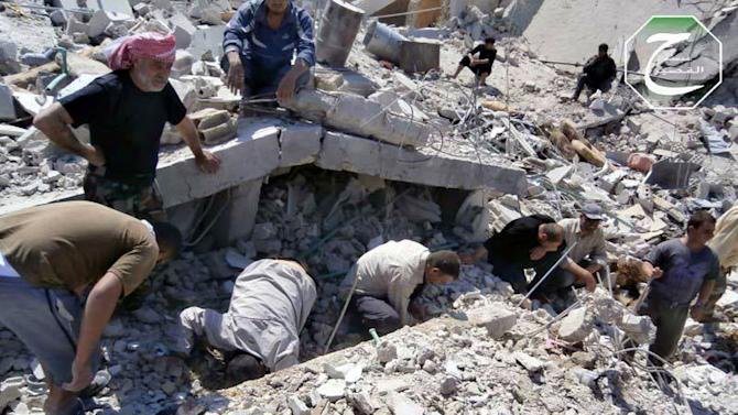 This citizen journalism image provided by Qusair Lens, which has been authenticated based on its contents and other AP reporting, shows Syrian citizens inspecting the rubble of damaged buildings that were damaged from a Syrian forces air strike in the town of Qusair, near the Lebanon border, Homs province, Syria, Tuesday, May 21, 2013. Several members of Lebanon's militant Hezbollah group died of wounds sustained while fighting for control of a strategic Syrian town near the Lebanese border, activists said Tuesday, as the battle in the area raged for its third straight day. (AP Photo/Qusair Lens)