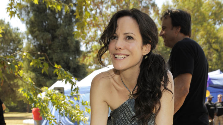 "Mary-Louise Parker, star of the Showtime series ""Weeds,"" poses behind a cake to celebrate the show's 100th episode, Tuesday July 17, 2012, in Los Angeles. ""Weeds"" is in its final season and will end its eight-year run in September. (Photo by Chris Pizzello/Invision/AP)"