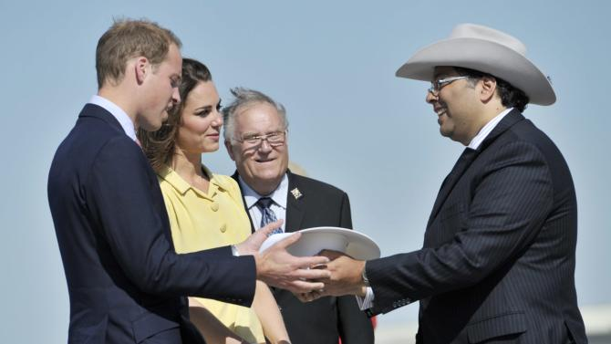 William and Kate, the Duke and Duchess of Cambridge, are presented white cowboy hats by Calgary Mayor Naheed Nenshi, right, and Alberta Lieutenant Governor Donald S. Ethell upon on their arrival to Calgary, Alberta Thursday, July 7, 2011. (AP Photo/The Canadian Press, Nathan Dentte)