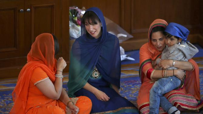 Samantha Cameron, Britain's Prime Minister David Cameron's wife, sits with Parliamentary candidate Priti Patel in the  Guru Nanak Darbar Gurdwara during the  Vaisakhi Festival in Gravesend