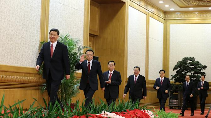 In this photo released by China's Xinhua news agency, China's new leaders, from left, Communist Party General Secretary Xi Jinping, Li Keqiang, Zhang Dejiang, Yu Zhengsheng, Liu Yunshan, Wang Qishan, and Zhang Gaoli, arrive for a press conference after being elected members of the Standing Committee of the Political Bureau of the 18th Central Committee of China's Communist Party at the Great Hall of the People in Beijing Thursday, Nov. 15, 2012. Xi will lead a new seven-member collective leadership of technocrats: Li, the presumptive premier; Vice Premier Zhang Dejiang; Shanghai party secretary Yu; propaganda chief Liu; Vice Premier Wang; and Tianjin party secretary Zhang Gaoli. (AP Photo/Xinhua, Ding Lin) NO SALES