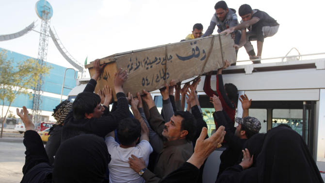 Family members of Hussein Abdullah, 22, who was killed in a car bomb attack, load his coffin onto a vehicle before transporting the coffin for burial in Najaf, 100 miles (160 kilometers) south of Baghdad, Iraq, Sunday, Feb. 17, 2013. A series of car bombs exploded within minutes of each other as Iraqis were out shopping in and around Baghdad on Sunday, killing and wounding scores of people, police said. (AP Photo/ Alaa al-Marjani)