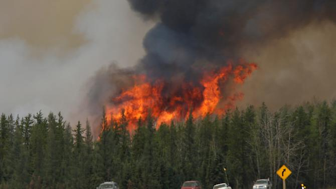 A wildfire burns as evacuees who were stranded north of Fort McMurray, Alberta, Canada head south of Fort McMurray on Highway 63
