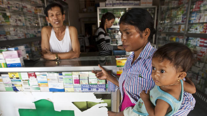 FILE - In this Aug. 26, 2009 file photo, a merchant speaks with a woman holding her ill child at a pharmacy in Pailin, Cambodia. The future of a pricey malaria program meant to provide cheap drugs for poor patients may be in jeopardy after health officials clashed over its effectiveness in two new reports. In 2010, the Affordable Medicines Facility for malaria was started by groups including United Nations agencies and the Global Fund to Fight AIDS, Tuberculosis and Malaria. It was a pilot project to subsidize artemesinin combination drugs. Most of the drugs bought were sold in the private sector, where there are few controls on who gets them. But in October 2012, a report by Oxfam, an international charity, labeled the program a failure and said there was no proof it had saved lives because officials didn't track who received the drugs. (AP Photo/David Longstreath, File)