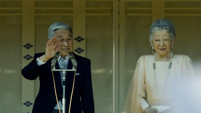 Japan's Emperor Akihito stands next to Empress Michiko as he  waves to well-wishers gathered to celebrate his 81st birthday at the Imperial Palace in Tokyo