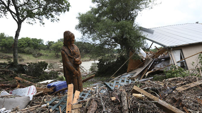 A carving of St. Francis of Assisi stands amid debris next to a destroyed home on River Road in Wimberley, Texas, Monday, May 25, 2015. Around a dozen people were reported missing in flash flooding from a line of storms that stretched from the Gulf of Mexico to the Great Lakes. (Jerry Lara/The San Antonio Express-News via AP)