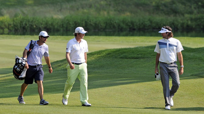 Master champion Bubba Watson, right, and U.S. Open Champion Webb Simpson, center, share a moment on the 15th fairway at the Travelers Championship golf tournament in Cromwell, Conn., Thursday, June 21, 2012. Both shot 66's to finish their rounds 4-under par. (AP Photo/Fred Beckham)