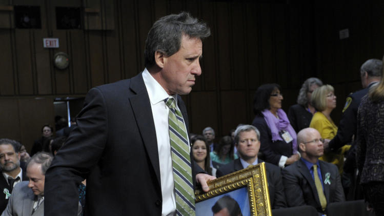 FILE – In this Feb. 27, 2013, file photo Neil Heslin, the father of Jesse, a six-year-old boy who was slain in the Sandy Hook massacre in Newtown, Conn., on Dec. 14, carries a picture of his son prior to testifying on Capitol Hill in Washington before the Senate Judiciary Committee on the Assault Weapons Ban of 2013. Families of the school shooting victims are making regular appearances with President Barack Obama and walking the halls of Congress to advocate for stricter gun regulations. They helped push through the nation's most restrictive firearms law in Connecticut this April. (AP Photo/Susan Walsh, File)