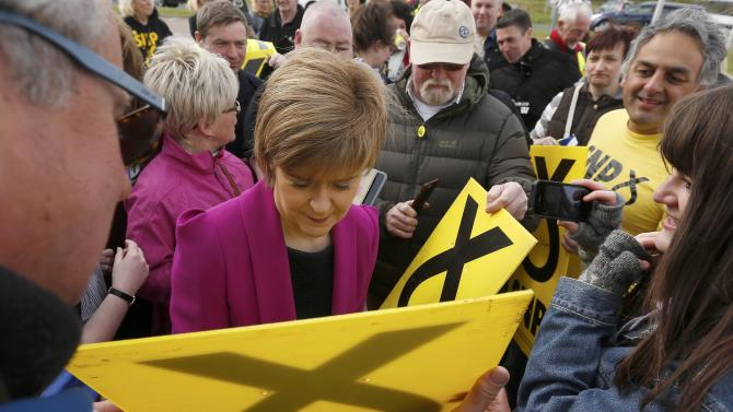 Nicola Sturgeon, the leader of the Scottish National Party, autographs campaign placards duing a visit to the Cook School during a campaign event, in Kilmarnock, Scotland