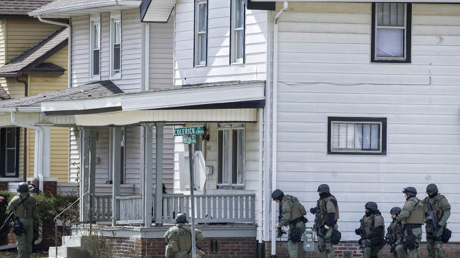 Armed officers surround a house Wednesday, March 20, 2013 in Fort Wayne, Ind., where police say a man suspected of killing a bus passenger earlier in the day is holding a 3-year-old child hostage. Police say the suspect is holed up the house near the street where a woman was pulled off a bus and fatally shot earlier in the day. (AP Photo/The Journal Gazette, Swikar Patel)