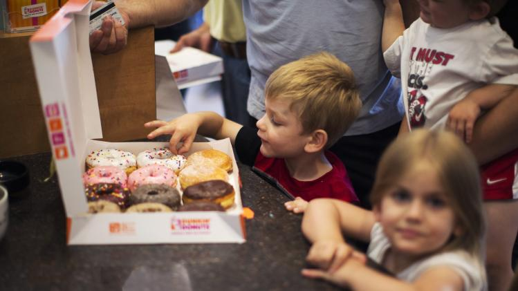 Dilan Nurkovic, 3, picks off a donut at a newly opened Dunkin' Donuts store in Santa Monica