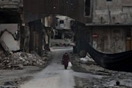 "A Syrian woman crosses a street next to a long black cloth used to separate the area from Syrian government forces' sniper fire, in the Bab el-Adid district in Aleppo on October 23. Peace envoy Lakhdar Brahimi said Wednesday that Syria and ""most"" rebel chiefs have agreed to a truce this week, boosting hopes of a breakthrough in the conflict, but the main armed opposition group was sceptical"