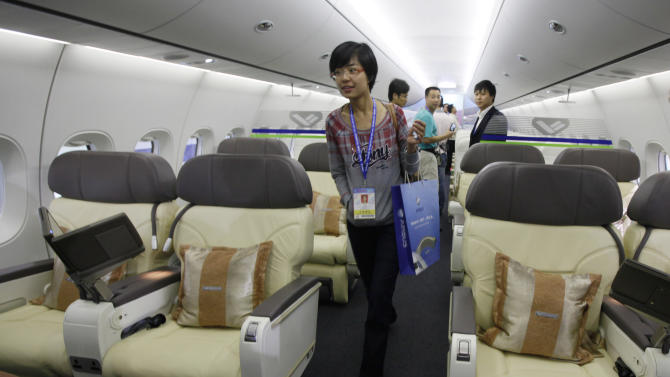 Visitors walk inside the cabin of a scale model of a Chinese-made C919 passenger airliner at the 8th China International Aviation and Aerospace Exhibition (Zhuhai Airshow) in Zhuhai, southern coast of Guangdong province, China, Tuesday, Nov. 16, 2010. The airshow will run from Nov. 16 to 21. (AP Photo/Kin Cheung)
