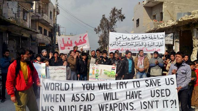 "This citizen journalism image provided by Edlib News Network, ENN, which has been authenticated based on its contents and other AP reporting, shows anti-Syrian regime protesters carry banners during a demonstration, at Kafr Nabil town, in Idlib province, northern Syria, Friday, Feb. 15, 2013. Heavy fighting for control of the international airport in the northern Syrian city of Aleppo and a major military air base nearby has killed some 150 rebels and government soldiers over the past two days, activists said Friday. The Arabic banner, background right, reads: ""prepare a clear roadmap backed by all those in the revolution inside the country that be put forward for the people before the West."" (AP Photo/Edlib News Network ENN)"