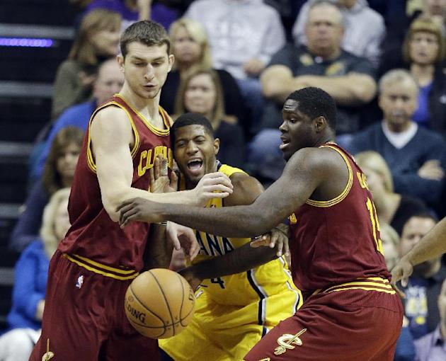 Indiana Pacers' Paul George, middle, battles for a loose ball against Cleveland Cavaliers' Tyler Zeller, left, and Anthony Bennett during the first half of an NBA basketball game Saturday, Nov. 2, 201