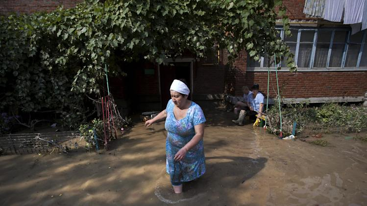 A local resident walks at a flooded house in Krimsk, about 1,200 kilometers (750 miles) south of Moscow, Russia, Sunday, July 8, 2012. The death toll from severe flooding in the Black Sea region of southern Russia has risen to at least 150. (AP Photo/Ignat Kozlov)