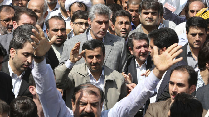 Escorted by his bodyguards, Iranian President Mahmoud Ahmadinejad, center, waves to his well wishers as he attends an annual nation-wide pro-Palestine rally known as Quds Day, while a demonstrator chants slogan in Tehran, Iran, Friday Aug. 26, 2011. Quds is the Arabic word for Jerusalem. (AP Photo/Vahid Salemi)