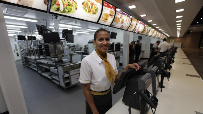 Rachel Lucian, assistant manager of the newly constructed McDonald's restaurant at the Olympic Park in east London, poses for the photographers, Monday, June 25, 2012. The restaurant is designed to be reusable and recyclable after the London 2012 Olympic and Paralympic Games. (AP Photo/Lefteris Pitarakis)