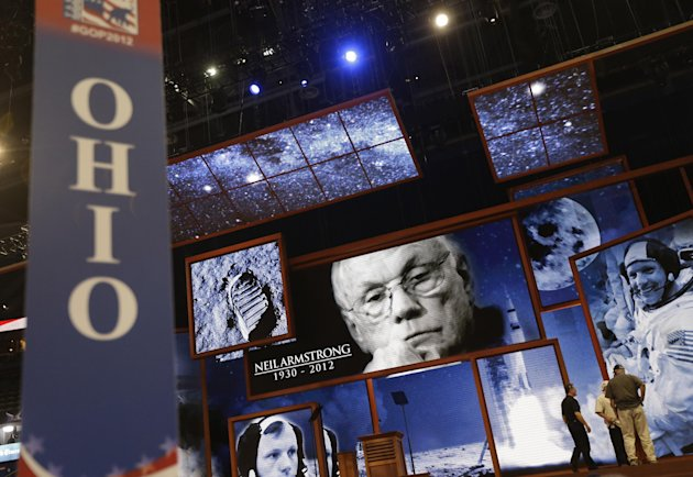 Behind the Ohio state delegate sign, pictures of Ohio native Neil Armstrong, the first man to walk on the moon, are displayed on the main stage the Republican National Convention in Tampa, Fla., on Sunday, Aug. 26, 2012. Armstrong died on Saturday. (AP Photo/David Goldman)