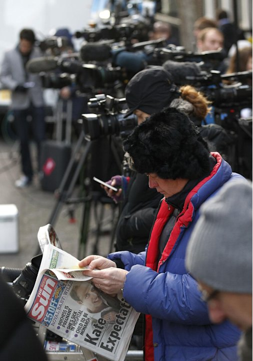 A journalist reads a copy of a national newspaper as media gather outside the King Edward VII hospital in central London where Kate, the Duchess of Cambridge has been admitted with a severe form of mo