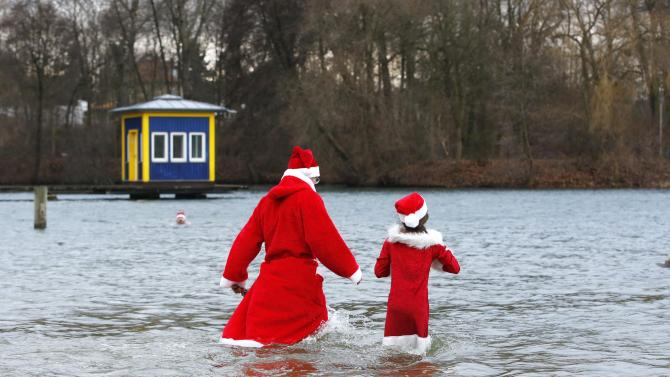 "Members of the ice swimming club ""Berliner Seehunde"" (Berlin Seals) take a dip in the Orankesee lake in Berlin as part of their traditional Christmas ice swimming session"
