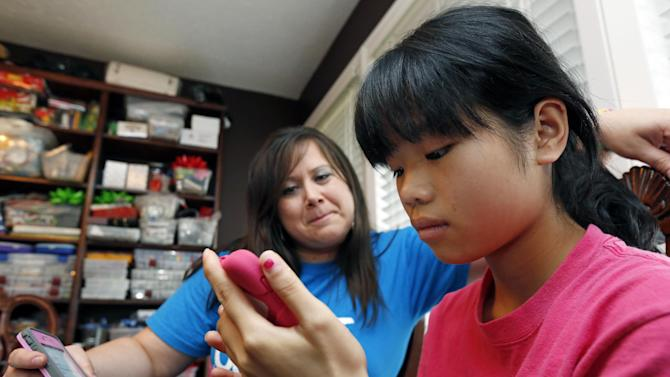 """In this April 4, 2013 photograph, Niki Smith watches her new 14-year-old daughter Guan Ya use Google Translate to """"speak"""" with her in their Rienzi, Miss., home. The Smiths and their three other children are using the program to communicate almost exclusively with Guan Ya, who is deaf. The family uses iPhones, iPods and a laptop, all loaded with the program to write in either English that translates to Chinese or vice-a-versa. (AP Photo/Rogelio V. Solis)"""