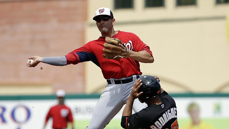 Miami Marlins' Josh Rodriguez, right, is out at second base as Washington Nationals' Danny Espinosa throws to first on a ground force out by Rafael Furcal in the third inning of an exhibition spring training baseball game, Saturday, March 15, 2014, in Jupiter, Fla