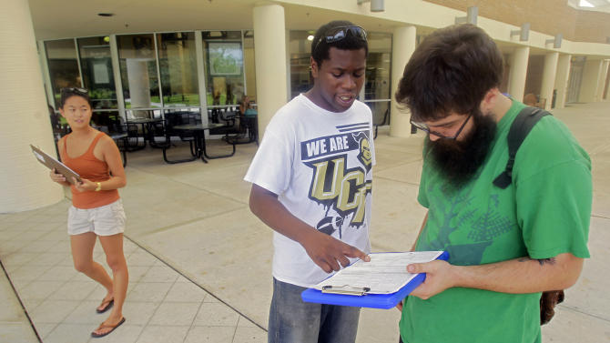 In this July 31, 2012, photo, Aubrey Marks, left, watches Jordan Allen, center, as he helps student Casey Eirhstaedt, right, register to vote at the University of Central Florida in Orlando, Fla. While most college campuses are relatively quiet, students at the University of Central Florida have taken it upon themselves to register their peers during the summer. Gone are the days when young voters weren't taken seriously. In 2008, they helped propel Barack Obama into the Oval Office, supporting him by a 2-1 margin. But that higher profile also has landed them in the middle of the debate over some state laws that regulate voter registration and how people identify themselves at the polls. (AP Photo/John Raoux)