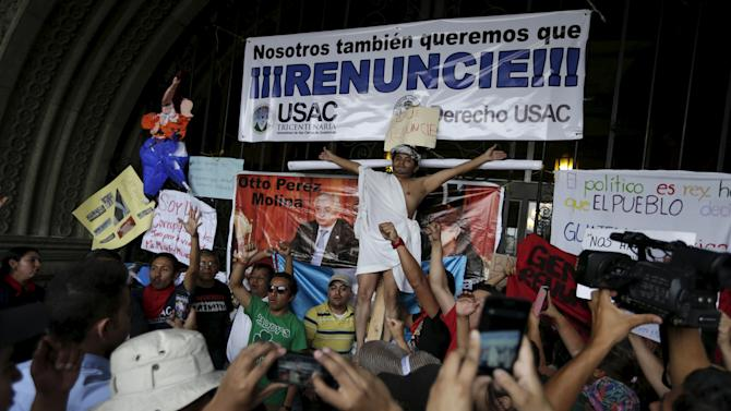 A man re-enacts the crucifixion in front of a banner with Guatemalan President Perez and Guatemalan VP Baldetti, during a demonstration against a political corruption scandal, at the door of Presidential Palace in downtown Guatemala City