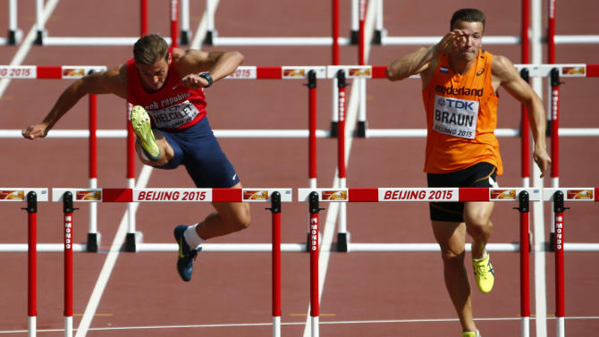 Helcelet clears a hurdle beside Braun during their 110 hurdles heat of the men's decathlon at the 15th IAAF Championships in Beijing