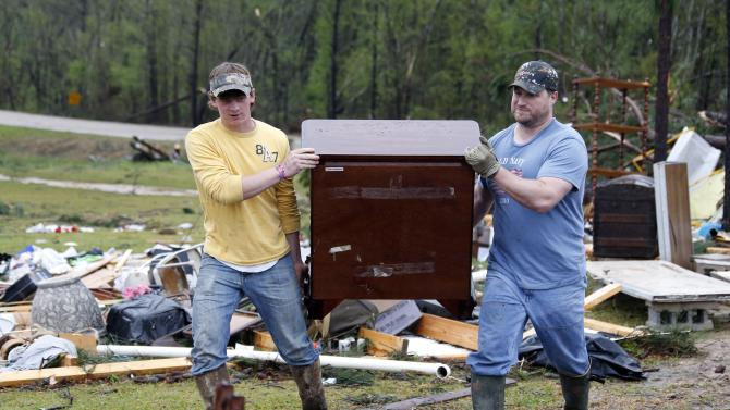 Shuqualak, Miss. residents begin cleanup of debris from homes hit by a tornado Thursday, April 11, 2013. A tornado plowed through rural sections of eastern Mississippi Thursday, killing at least one person and causing widespread damage and power outages, officials said. That and other damaging storms in the state were part of the same front that had dumped heavy, wet snow and ice in the Midwest and spawned tornadoes elsewhere.  (AP Photo/Rogelio V. Solis)