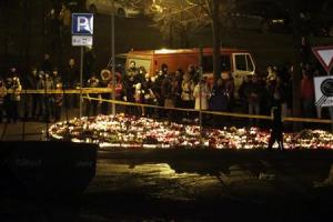 People gather near lit candles in front of a collapsed supermarket in capital Riga