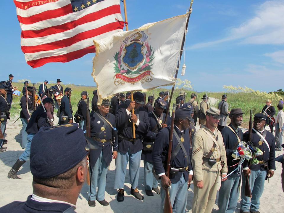 "Re-enactors prepare to lay a wreath on Morris Island near Charleston, S.C., on Thursday, July 18, 2013 during a observance of the 150th anniversary of the charge of the black 54th Massachusetts Volunteer Infantry in a fight commemorated in the film ""Glory."" (AP Photo/Bruce Smith)"