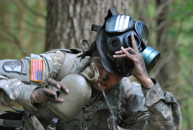 In a May 9, 2012 photo, Capt. Sara Rodriguez of the 101st Airborne Division pours water on her face during the expert field medical badge testing at Fort Campbell, Ky.,  Female soldiers are moving int