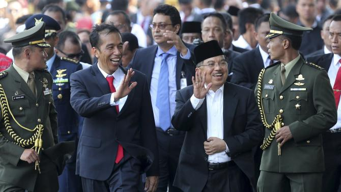 Indonesia's President Joko Widodo laughs as he walks with his Vice President Jusuf Kalla in Jakarta