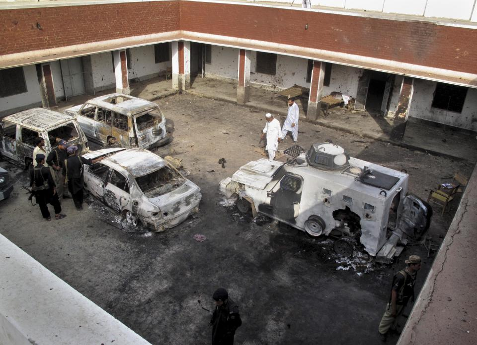 Pakistani police officers examine the damaged vehicles, a day after Taliban militants attacked at a police station, Sunday, June 26, 2011 in Kolachi near Dera Ismail Khan, Pakistan. The Pakistani Taliban say they used a female suicide bomber for the first time in an attack on the police station in northwestern Pakistan. (AP Photo/Kashif Naveed)