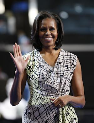 First Lady Michelle Obama waves as she appears on the stage for filming a campaign video at the Democratic National Convention inside Time Warner Cable Arena in Charlotte, N.C., on Monday, Sept. 3, 2012. (AP Photo/Jae C. Hong)