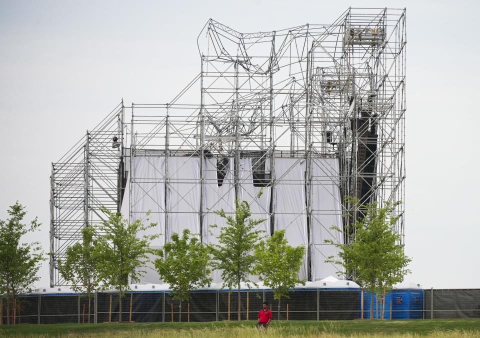 A man stands near a collapsed stage at Downsview Park in Toronto on Saturday, June 16, 2012.  Toronto paramedics say one person is dead and another is seriously hurt after the stage collapsed while setting up for a Radiohead concert. They say two other people were injured and are being assessed. (AP Photo/The Canadian Press, Nathan Denette)