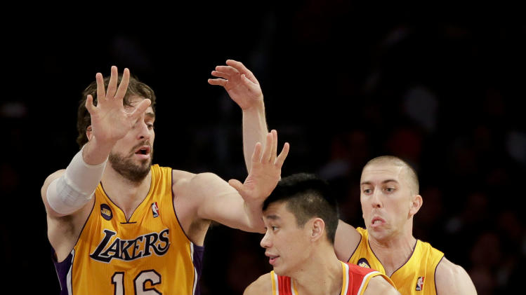 Houston Rockets' Jeremy Lin, center, drives against Los Angeles Lakers' Pau Gasol, left, of Spain, and Steve Blake during the first half of an NBA basketball game in Los Angeles, Wednesday, April 17, 2013. (AP Photo/Jae C. Hong)