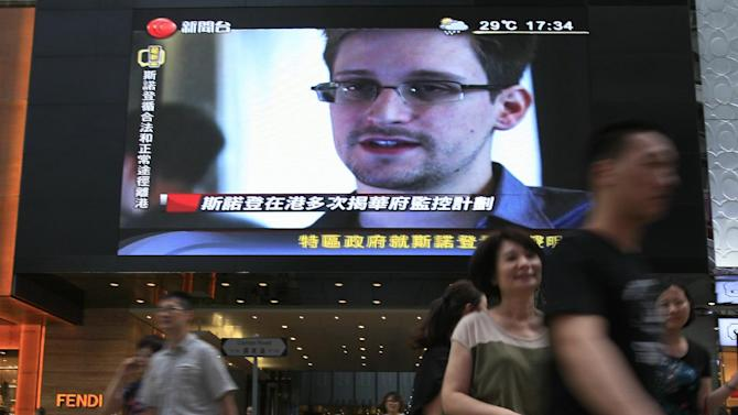 FILE - This June 23, 2013 file photo shows a TV screen shows a news report of Edward Snowden, a former CIA employee who leaked top-secret documents about sweeping U.S. surveillance programs, at a shopping mall in Hong Kong. U.S. intelligence agencies are scrambling to salvage their surveillance of al-Qaida and other terrorists who are working frantically to change how they communicate after a National Security Agency contractor leaked details of two NSA spying programs. It's an electronic game of cat-and-mouse that could have deadly consequences if a plot is missed or a terrorist operative manages to drop out of sight. (AP Photo/Vincent Yu, File)