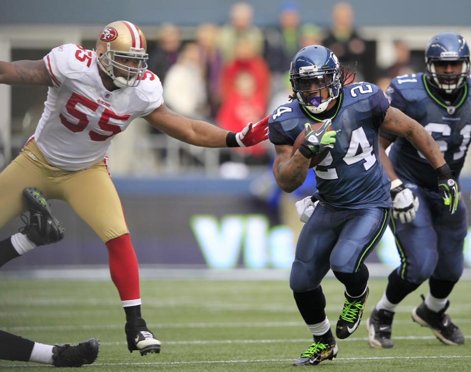 Seattle Seahawks'  Marshawn Lynch carries the ball with San Francisco 49ers'  Ahmad Brooks defending in the first half of an NFL football game in Seattle Saturday, Dec. 24, 2011. (AP Photo/John Froschauer)