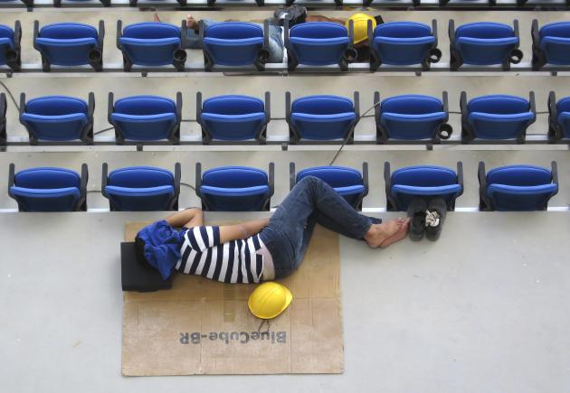 Construction workers take a nap on their lunch break inside the Arena Das Dunas stadium as work continues in preparation for the 2014 FIFA World Cup soccer championship in Natal